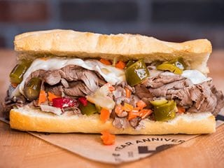 Sandwich with pickles, jalapeno, meat, carrots