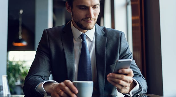 Businessman drinking coffee and using his smartphone