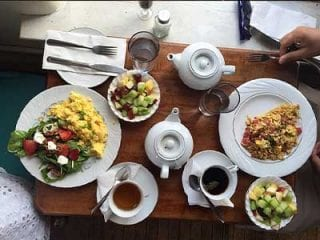 Table with Fruits, Scrambled eggs, coffee, tea