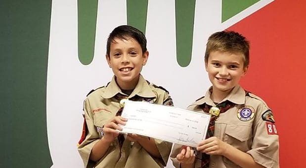 Two young scout boys holding check