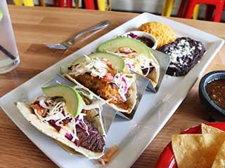 Plate with three tacos with avocados