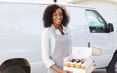 Woman in front of a Van with a box filled with muffins