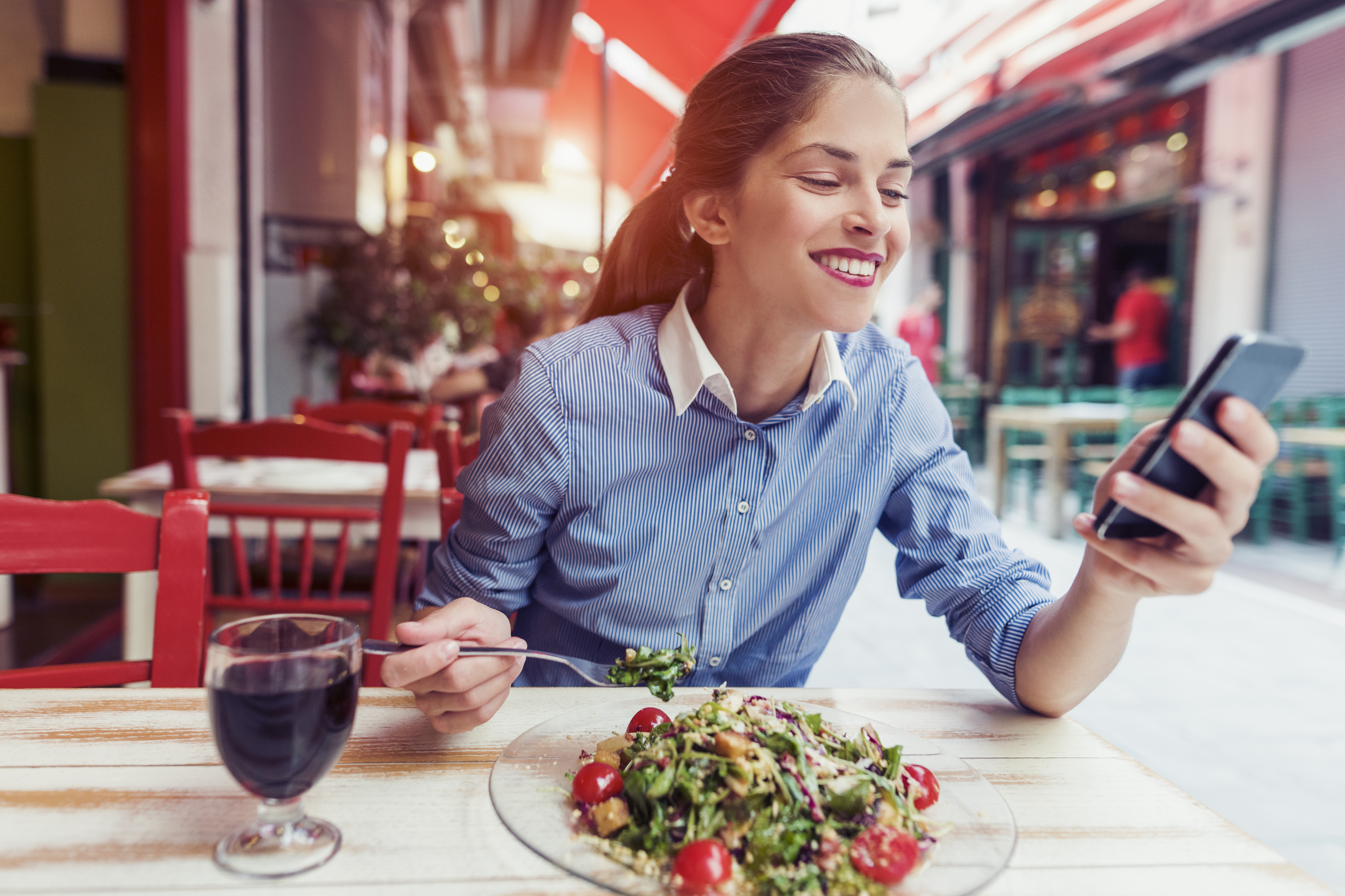 beautiful young woman using an application to send an sms message in her smartphone device while eating a saladbeautiful young woman using an application to send an sms message in her smartphone device while eating a salad