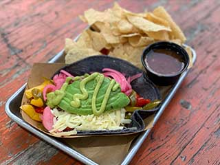 Veggie Taco served on a blue corn tortilla with grilled peppers avocado, pickled onion. cotija cheese.jalapeño ranch