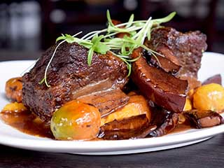 Beer braised short ribs served on a bed of carrot bredie and portobello red wine reduction