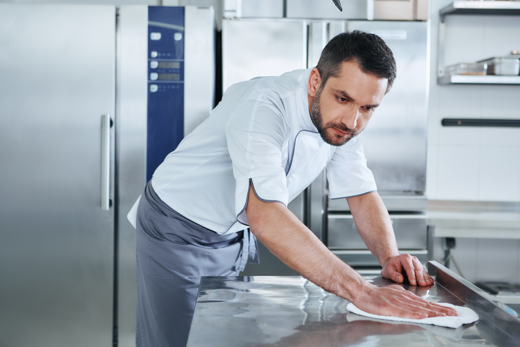 Bearded man prepares the surface for cooking in the kitchen