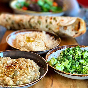 Green falafel, smoky hummus, baba ghanoush, marinated feta, pomegranate-tomato and parsley tabouli, served with seeded flatbread.