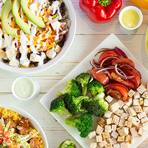 Plate with Broccoli, Tomatoes and Grilled Chicken. Salad Bowl with Avocado