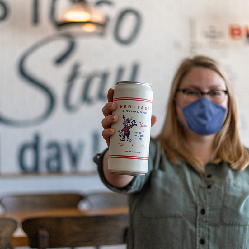 woman wearing a mask and holding a beer at Heritage Pizza and Taproom
